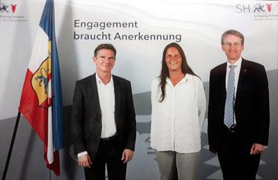 Bianca Rudloff mit Sozialminister Heiner Garg (links) und Ministerpräsident Daniel Günther. Foto: Jessen Fotografie Plön