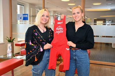 Spitzenschwimmerin Lotta Steinmann (links) nimmt von Julia Beckmann, Leiterin der Geschäftsstelle HanseBelt e.V., einen HanseBelt-Schwimmanzug entgegen. Foto: IHK/Tietjen