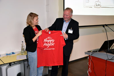 """Stormarns Landrat Dr. Henning Görtz freute sich über ein T-Shirt mit der Aufschrift: """"HanseBelt Botschafter"""", das Julia Beckmann von der HanseBelt-Geschäftsstelle ihm überreichte. Foto: IHK/Özren"""