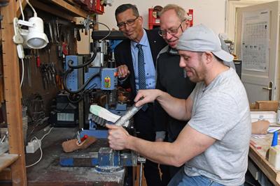 Markus Dusch (v.l.) und Klaus-Dieter Schoofs beobachten Malte Hansen dabei, wie er einen Gipsabdruck für die Einlagenfertigung bearbeitet. Foto: Arbeitsagentur.