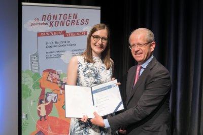 Laudator Prof. Dr. Gerhard Adam überreicht den Promotionspreis der Deutschen Röntgengesellschaft 2018 an Dr. Thekla Oechtering. Foto: DRG / Thomas Rafalzyk