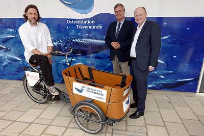 Thorsten Walter und de Vereinsvorsitzende Ulrich Krause bekamen das Lastenrad von Oke Heuer, Vorstandsmitglied der Sparkasse zu Lübeck, überreicht. Fotos: Karl Erhard Vögele
