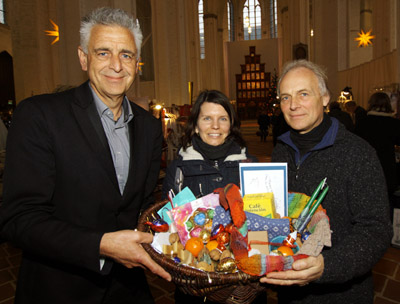 Pastor Dr. Bernd Schwarze (links) und Frank Peschlow (rechts) überraschten Stephanie Tremmel mit einem Präsentkorb. Fotos: JW