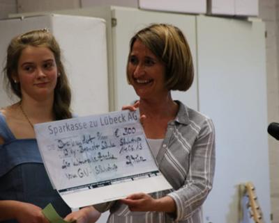 Schulleitung Alexandra Hase-Rodriguez mit Schülerin bei der Scheckübergabe. Foto: Gemeinnütziger Verein Lübeck-Schlutup e.V.