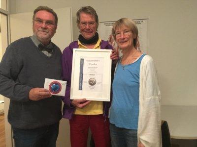 Harald Werner nimmt dankend die großzügige Spende vn Nuriama und Rainer Lichterstein entgegen. Foto: Praxis ohne Grenzen e.V.
